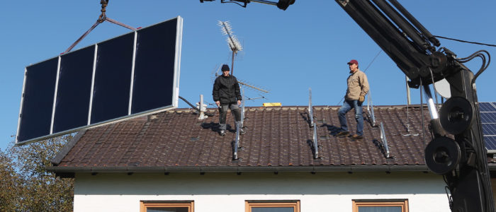 STARNBERG, GERMANY - OCTOBER 15:  Workers wait for the crane to get installed solar power modules for producing heat on the roof of a house on October 15, 2011 in Wessling, Germany. Germany has and is continuing to invest heavily in solar energy, both in the public and private sectors. The German government introduced a feed-in tariff with its Renewable Energy Act in 2000 that guarantees homeowners a minimum rate for selling electricity from renewable energy sources into the nation's electricity grid.  (Photo by Alexandra Beier/Getty Images)